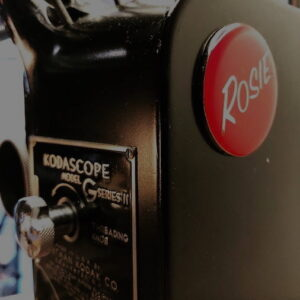 Up close shot of a Rosie's Workshop Badge on a vintage projector table light.