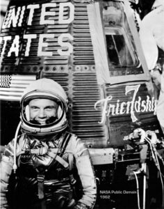 Astronaut John Glenn beside NASA's Friendship 7 capsule. NASA public domain.