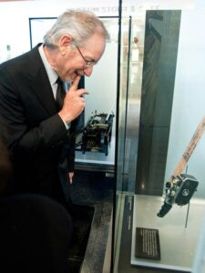Steven Spielberg looking at his Bolex 8mm in the Museum.