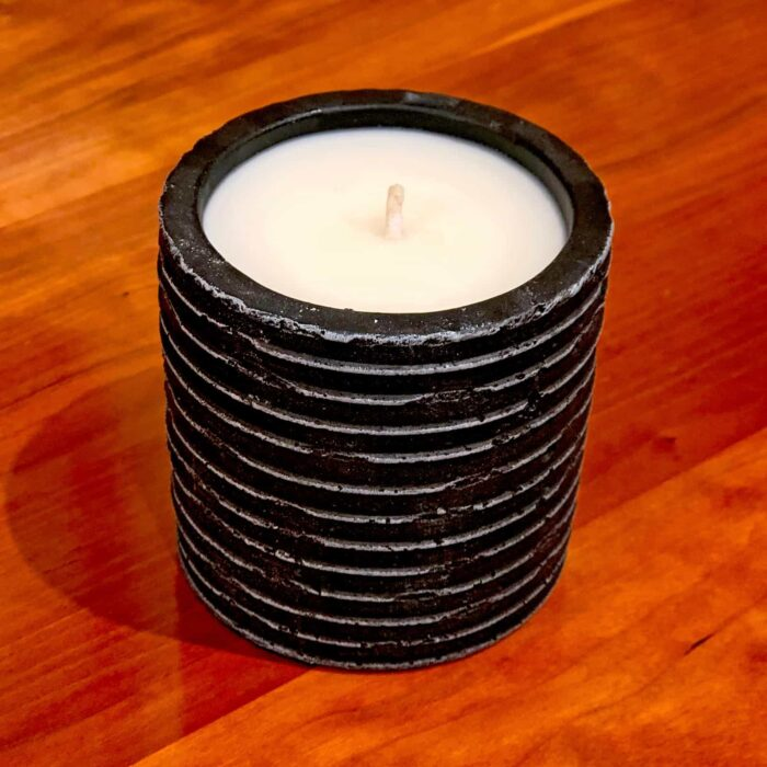 Close-up view of Rosie's Workshop small black Story Candle. Hand crafted, 100% pure soy wax, cosmetic grade scents, the finest cotton made wicks. Storytelling through smell & fire.